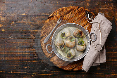 Bourgogne Escargot Snails with garlic herbs butter in aluminum pan on rustic wooden background copy space