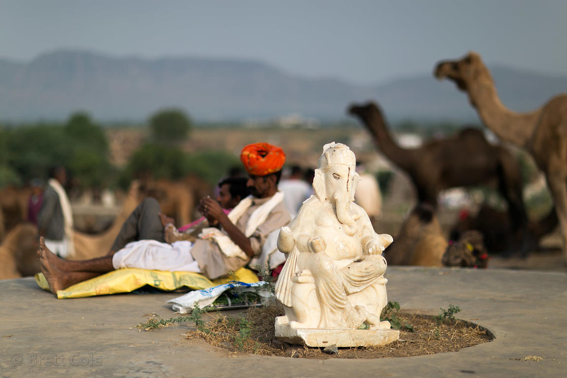 Camel herders relax near a small statue of Ganesh, Pushkar, Rajasthan, India