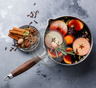 Mulled wine hot drink with citrus, apple and spices in aluminum casserole on concrete background