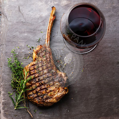 Grilled beef barbecue Veal rib Steak on bone and red wine on stone slate background