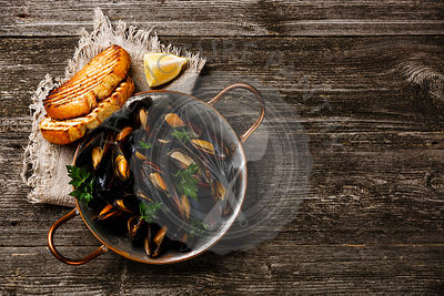 Mussels Clams in copper cooking dish pan and toasted bread on wooden background copy space