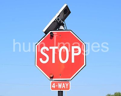 Stop sign with solar panel on top of the sign