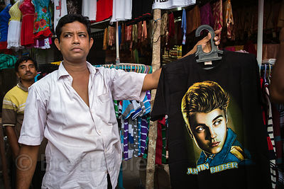A man sells a Justin Beiber t-shirt at a market in Gariahat, Kolkata, India