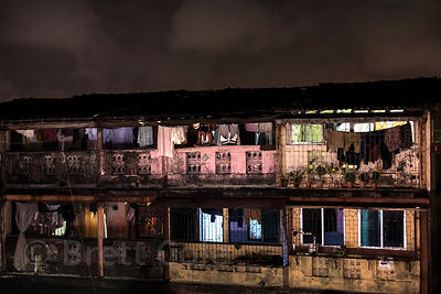 Nighttime view of weathered apartment buildings near Bandra Railway Station, Mumbai, India. Taken from the elevated Bandra Sk...