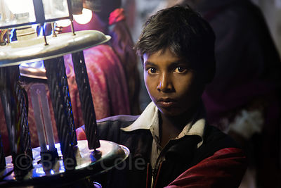 A boy carries a lantern during a marriage procession, Badi Basti, Pushkar, Rajasthan, India. Low caste children are employed ...