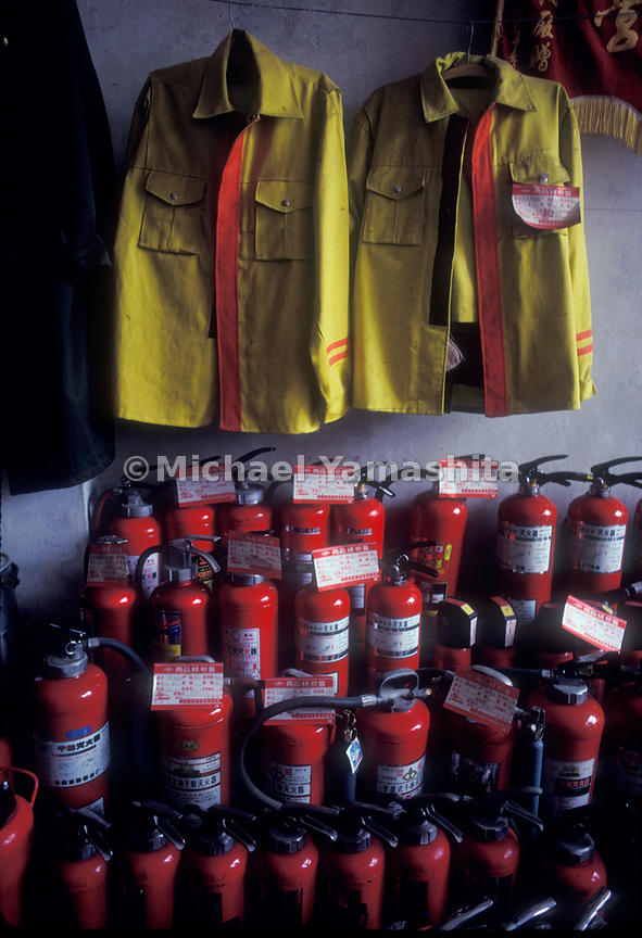 Fire jacket and fire extenguishers inside a firehouse.