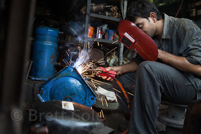 A welder works at his shop in the Dharavi slum, Mumbai, India.