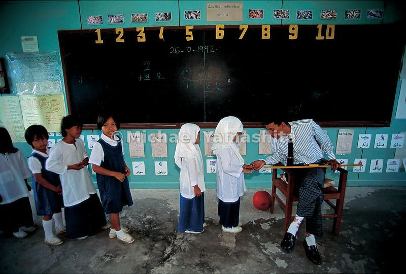 Schoolchildren queue for a fingernail check-up in a Brunei classroom.