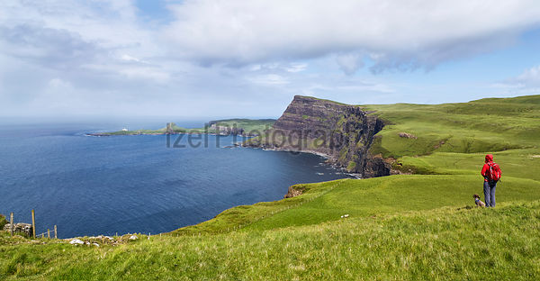 A hiker and their dog looking out over the sea cliffs of Ramasaig with Neist Point in the distance. Isle of Skye, Scotland, UK.