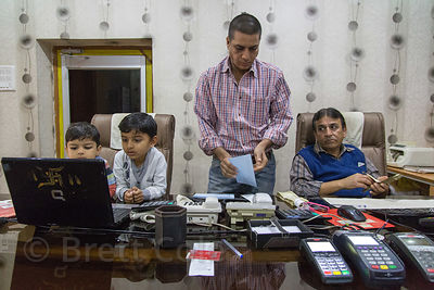 Father and children working at a money exchange, Pushkar, Rajasthan, India