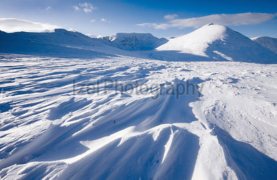 Wind swept snow formations in the Lake District with Striding Edge, Helvellyn, Swirral Edge & Casty Cam in the distance.