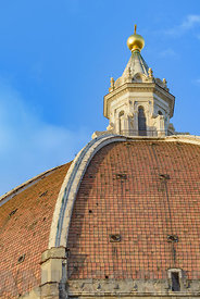 The great dome of the Duomo of Florence against a blue sky.