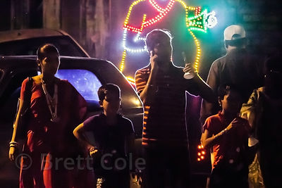 A man talks on a mobile phone at night in front of LED displays for the Durga Puja festival, Lake Gardens, Kolkata, India.