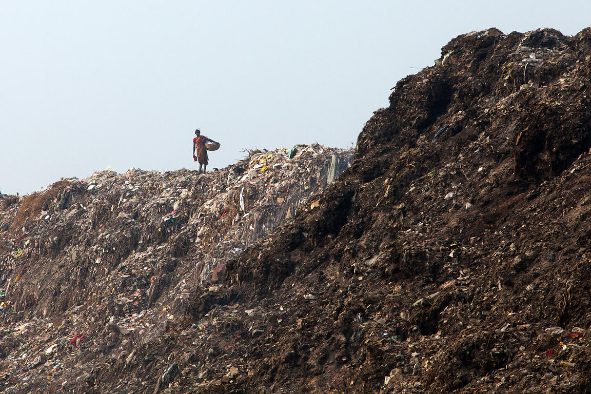 A woman collecting scrap for recycling stands on top of the Dhapa landfill, Kolkata, India. Dhapa is the main landfill for Ko...