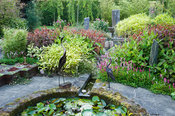 The Carpet Garden features standing stones and a rill that empties into a circular pond beside which two metal birds stand gu...