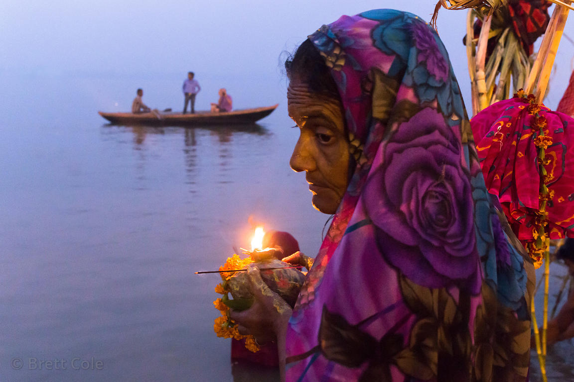 A woman prays at sunset along the Ganges River during Chhath Puja, Varanasi, India. Chhath Puja is a devotion to the Sun God ...