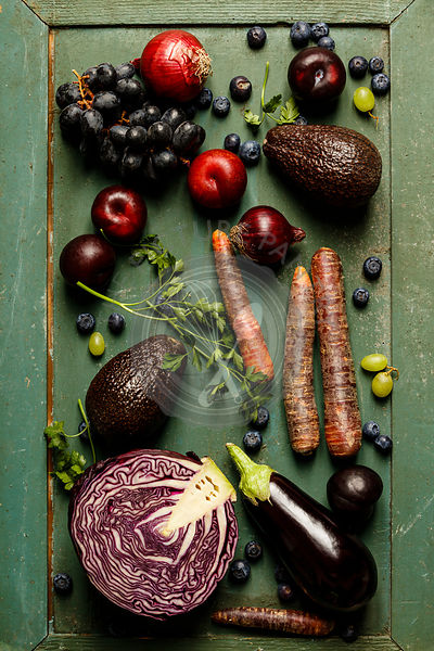 Assortment raw organic of purple ingredients: eggplants, onions, berries, carrots, grapes, cabbage, avocado, plums over rusti...