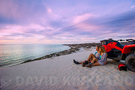 Couple watching the sunset on the sand dune at Coral Bay, Western Australia