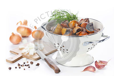 Raw wild mushrooms with spices for cooking on white background