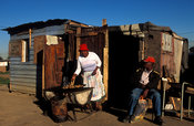 woman cooking outside her shack, Langa, Cape Flats, Cape Town, South Africa