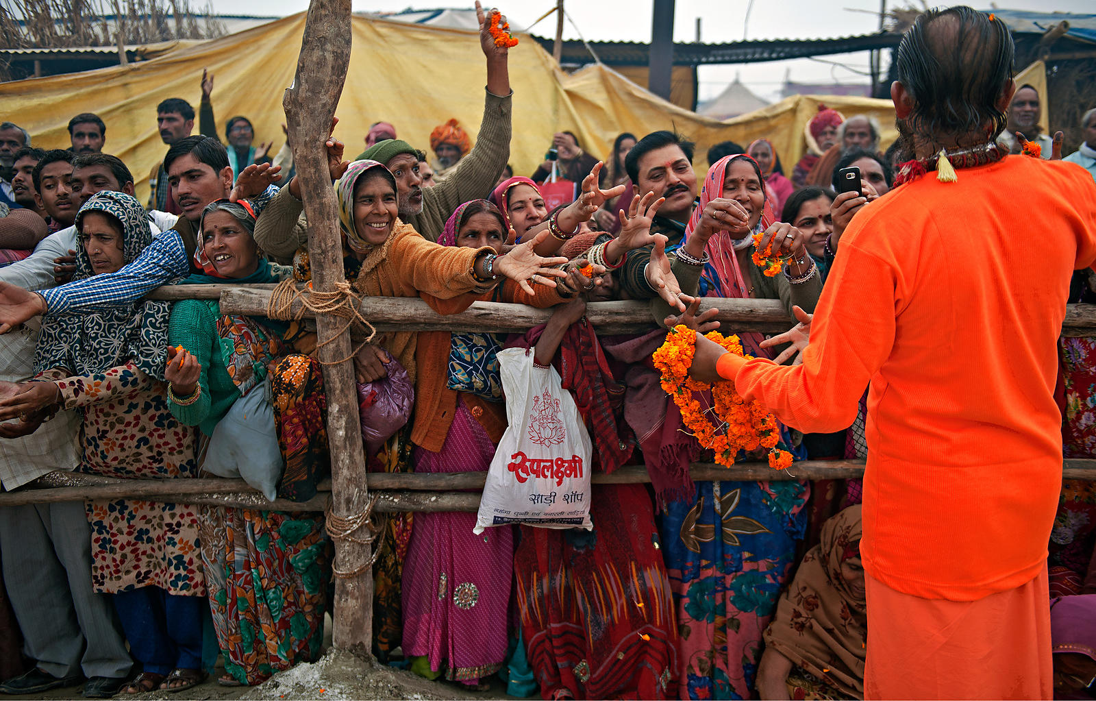 Pilgrims wait for their turn to get the blessings from the saint at the Kumbh Mela, Allahabad