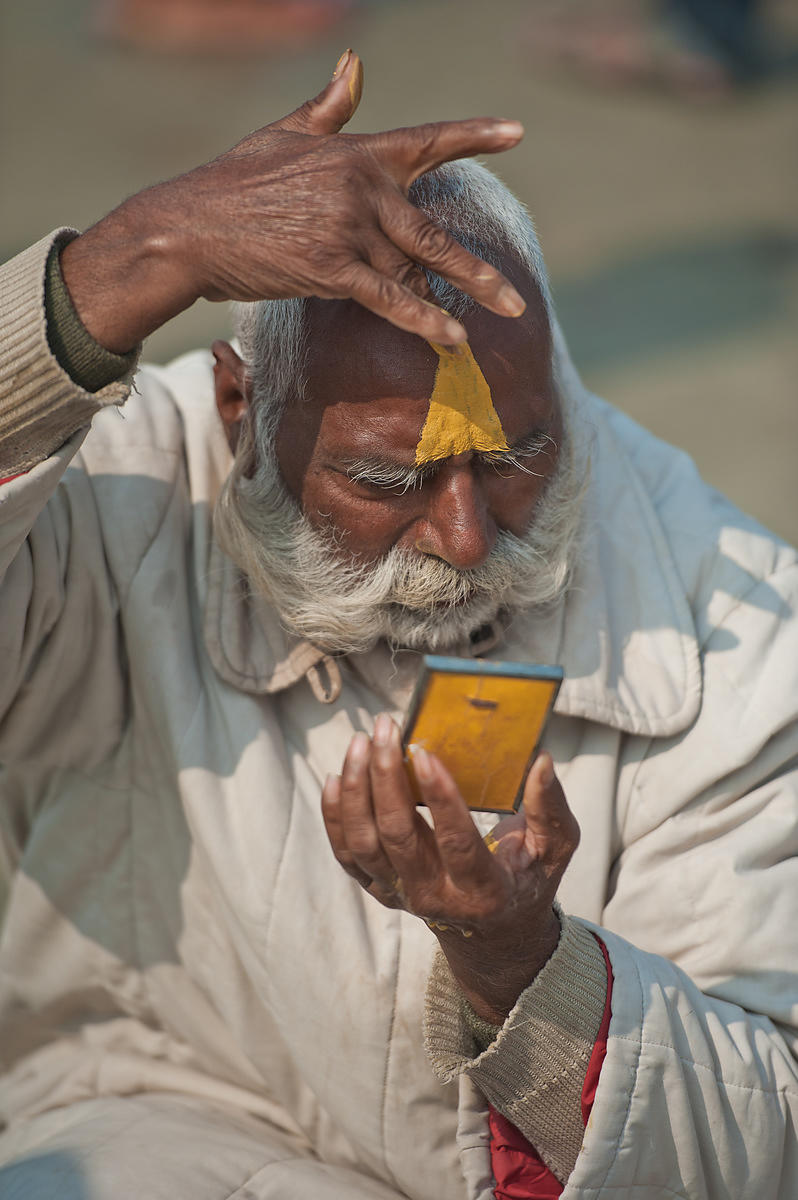This portrait of an old man applying tilak on his forehead was shot during the Kumbh Mela, Allahabad.