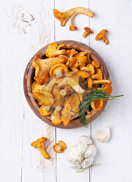 Raw chanterelles in  wooden bowl on white background texture