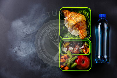 Take out food Lunch box with Croissant sandwich, Greek salad and vegetables with bottle of water on blackboard background cop...