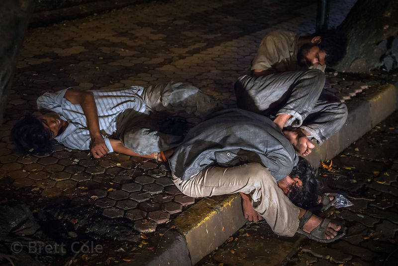 Men who have either passed out drunk or are sleeping after a hard day's work at a construction site, or borh. On the street i...