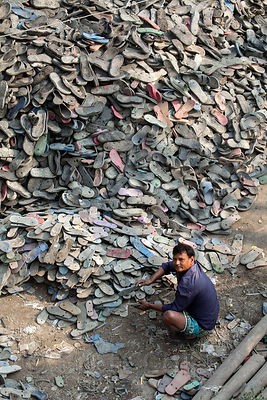 A man recycles flip-flop sandals in Dhapa, Kolkata, India. Dhapa is the site of Kolkata's main landfill, and a large number o...