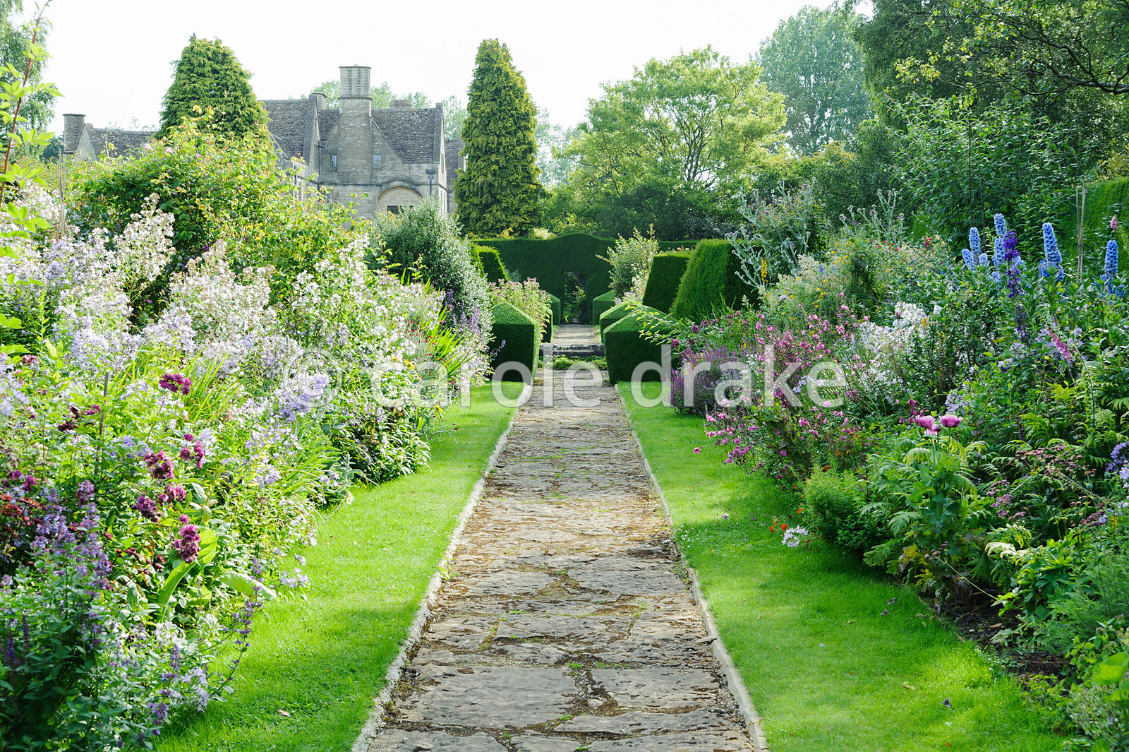 Double herbaceous borders framed with clipped box and tall yew hedges include delphiniums, phlox, campanulas and poppies. Rod...