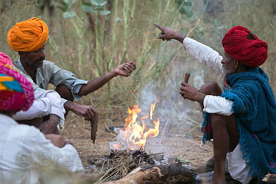 Farmers smoke tobacco chillum during the Pushkar Camel Fair, Pushkar, Rajasthan, India