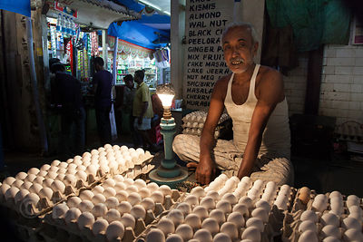 An egg seller in Newmarket, Kolkata, India. He uses the light to examine the eggs for purity.