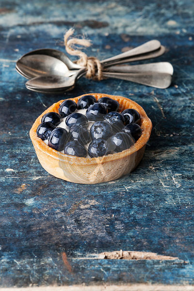 Blueberry tart on blue wooden background