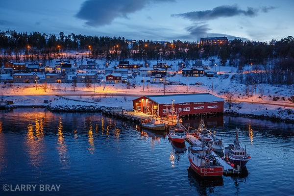 Boats and houses in the snow in the harbour at dusk, Alta, Norway