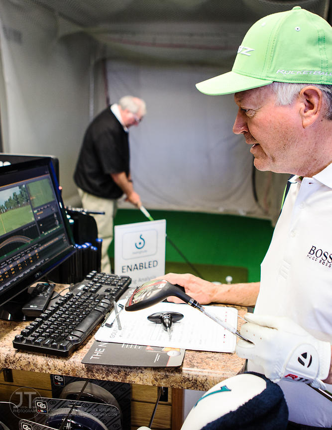 Avid golfer Jim Barth and friend Jon Styre test clubs on a Swingbyte enabled computer swing analyzer bay with shop owner Bruc...