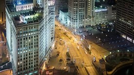 Bird's Eye: Medium Shot of A Pulsating Michigan Avenue Below the Historic Wrigley Clock Tower at Night