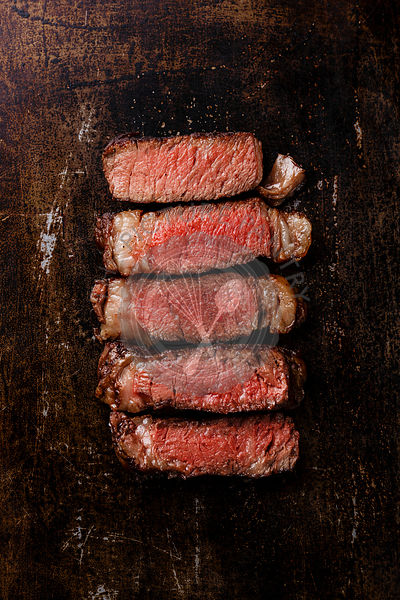 Slices of grilled meat barbecue steak Rib eye medium rare on dark metal background