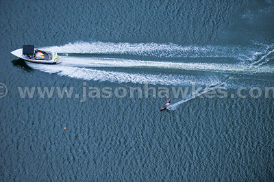 Aerial view of speedboat and waterskiier