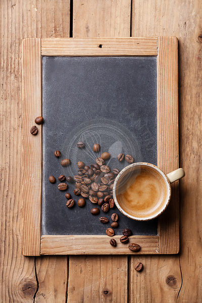 Coffee cup with coffee beans on vintage slate chalk board