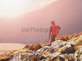 A hiker and their dog walking down the mountain ridge of Scar Crags and Causey Pike with the early morning sun in the English...