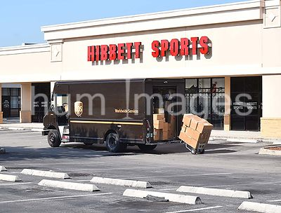 UPS delivery driver unloading truck at Hibbett Sports store at strip mall