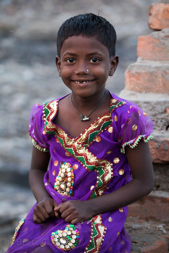 A girl smiles for a portrait near the Dhapa landfill, Kolkata, India. Hundreds of people work at farms and recycling faciliti...