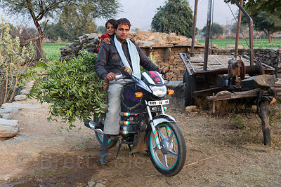 A man and his daughter transport goat fodder by motorcycle, Kharekhari village, Rajasthan, India