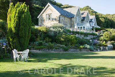 Lawn below house with table and chairs. The Shute, nr Ventnor, Isle of Wight, UK