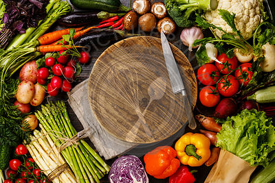Fresh vegetables around round wooden cutting board copy space