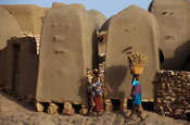 Women carrying millet in front of mud granaries, Sanga, Dogon Country, Mali