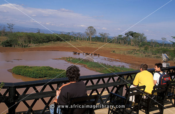 Tourists overlooking the waterhole at Treetops hotel, Aberdares National Park, Kenya