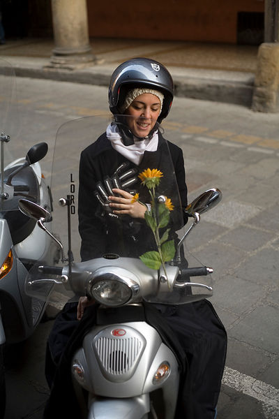 Italy - Bologna - A woman on her scooter decorated with fresh flowers