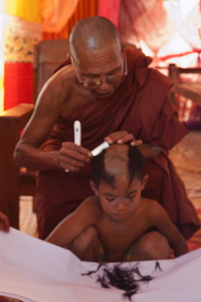 Monk shaving head of boy
